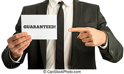 Closuep of businessman pointing to a white card with a Guaranteed sign on it