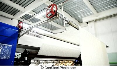 Cloth is sewed with using spinning machine on the plant closeup.