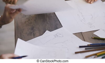 Clother designers woman creates a sketch on the paper closeup in tailor studio