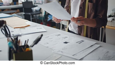 Clothes designer holding drawings of clothes working in...