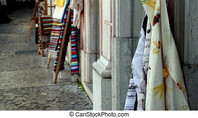 Clothes displayed on the sidewalk small street with some cloths on a wooden pole
