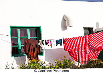 clothes drying in front of a fishermans house at the harbor