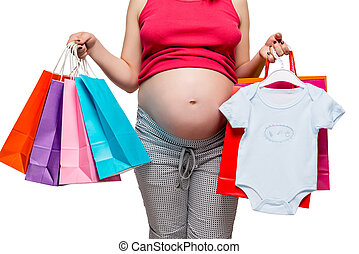 Clothes for her son and other purchases in the hands of a pregnant woman, belly closeup