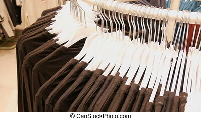 Clothes hanging on hangers of a large round stand in a...