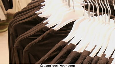 Clothes hanging on hangers of a large round stand in a clothing store in mall or shopping center