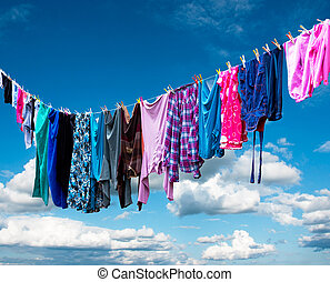 clothes hanging to dry on clothesline on blue sky