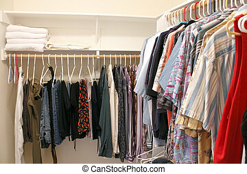 Clothes in a Closet - Mens wardrobe variety of pants and...