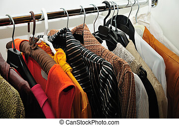 clothes in the wardrobe - bright colourful clothes hanging...