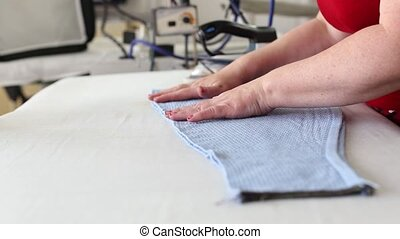 Clothes ironing with industrial equipment. Ironing garment....