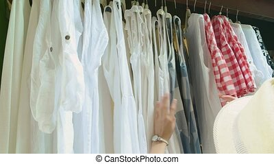 Clothes on hangers, female hands.