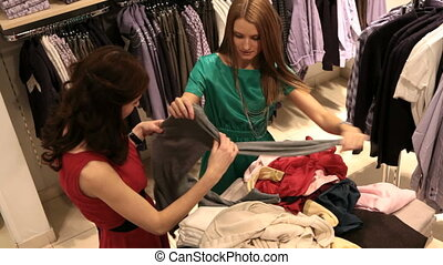 Young women looking for best pieces of clothes in the heap