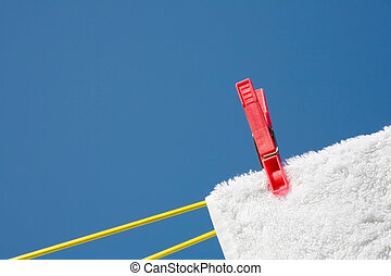 Clothes peg on a white towel and washing line against a blue...