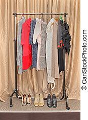 Clothes rack - Rack with fashionable clothes and shoes in...