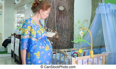 Clothes shopping in baby and maternity shop woman looking for summer dress and shoes