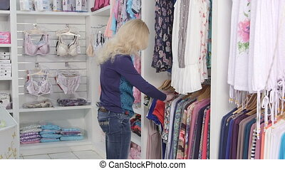 Clothes shopping in baby and maternity shop woman looking for summer dress