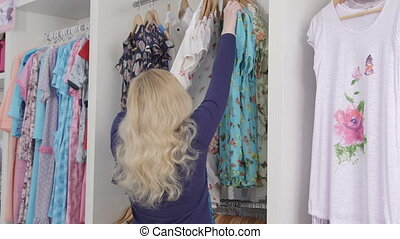Clothes shopping in clothing store woman looking for summer dress