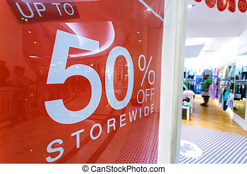 clothes storefront window with discount poster