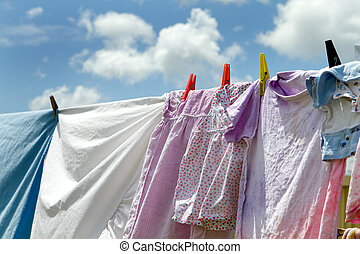 Children's clothes and bedsheets have been hung out to dry on a clothesline viewed against a blue sky with clouds.