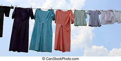 clothesline hung with hand-sewn garments drying out in the fresh air of a sunny day.