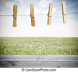 Clothespin on a laundry line outside above wooden boards...