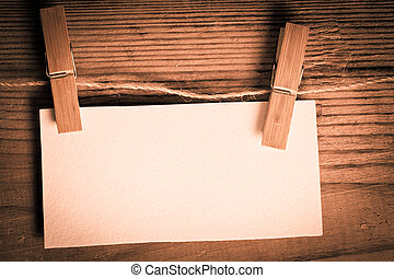 clothespin with blank white card on the wooden backgorund