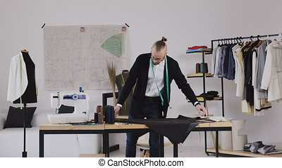 Clothing designer and tailor is working with measurements on a studio table. Manufacturer of clothes at a garment factory. Tailor at work, drawing line on fabric with chalk