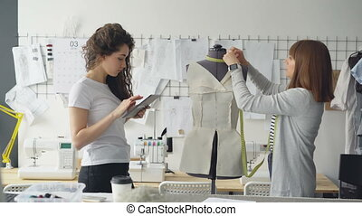Clothing designer entrepreneurs are measuring mannequin...