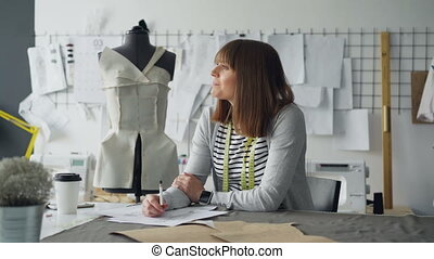 Clothing designer in small start-up business is drawing...