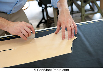 Clothing designer or tailor marking a pattern with chalk on...