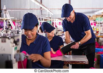 clothing factory foreman explaining work to machinist