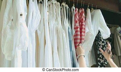 Clothing on hangers, female hands. Woman choosing clothes.