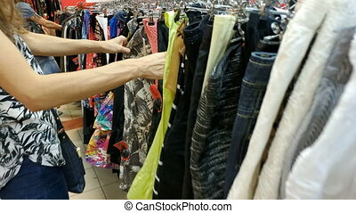 Clothing shop changing room. Caucasian young woman choosing her fashion outfit clothes in closet at home or store