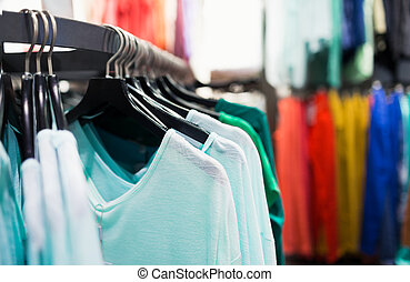 Clothing store - Fashionable colorful clothes on hangers in...