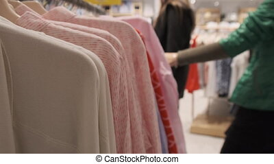 Clothing Store. Women's Clothing Hangs on Hangers Inside the Store. Buyers choose things. Boutique. Close-up. Shopping. A lot of clothes in various styles. Woman's hand runs along a row of clothes.