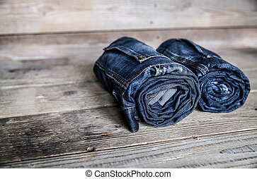 Clothing. twisted jeans on a wooden background