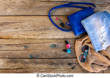 Clothing, women's accessories and cosmetics on old wooden background. Top view.