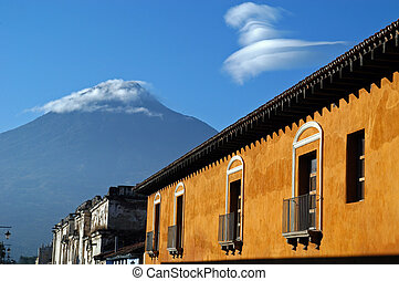 Cloud-capped volcano above old houses in Antigua, Guatemala.