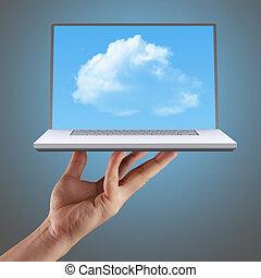 Cloud computing concept - hand shows cloud computing, laptop...
