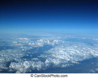 Cloud formations from the aeroplane window, deep blue sky.
