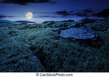 cloud over the grassy hillside with rocks at night in full...