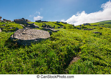 cloud over the grassy hillside with rocks. path uphill in to...