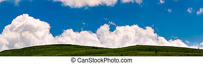 cloud rising behind the grassy hills