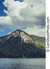 cloud shadow casting on the mountain in front of a lake