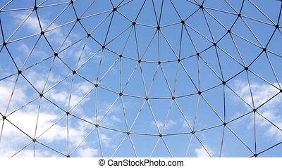 cloud timelapse shot through metal structure