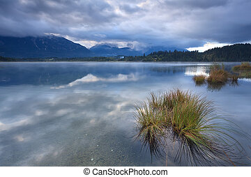 clouded dusk over Barmsee lake with view on Karwendel mountains