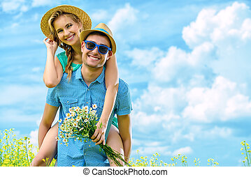 Happy young people in love on a meadow on a sunny summer day. Summer holidays. Love concept.