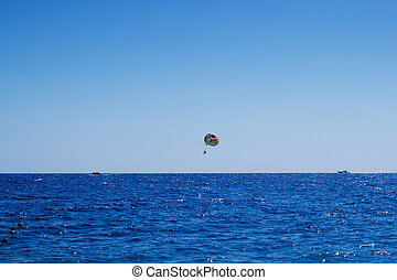 Cloudless day parasailing
