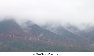 Clouds and fall colors - clip of clouds moving over a...