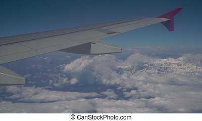 Clouds and Himalayas under the wing of an airplane