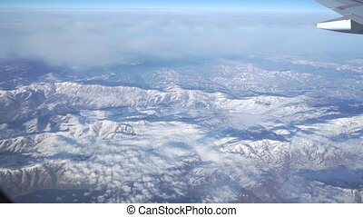 Clouds and mountains beneath the airliner. Aerial video